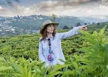 Bella donna graziosa nella condizione del cappello alle piantagioni di tè e nell'indicare la divagazione con il dito fotografia stock libera da diritti