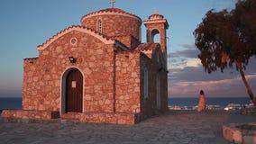 Bella donna greca che cammina vicino alla vecchia chiesa, esaminante vista sul mare stupefacente archivi video