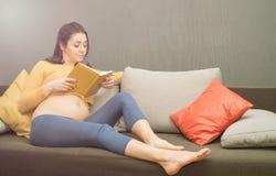Bella donna incinta in buona salute che si siede sullo strato e che reding Fotografie Stock
