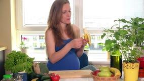 Bella donna incinta caucasica che mangia banana in cucina archivi video