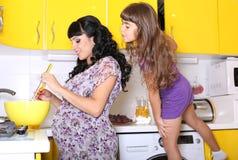 Bella donna incinta che cucina con la piccola figlia Fotografie Stock