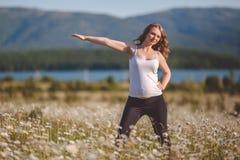 Bella donna incinta che fa gli sport nel campo della camomilla Immagine Stock