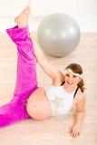 Bella donna incinta che fa le esercitazioni di forma fisica Fotografia Stock