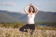 Bella donna incinta che fa yoga nel campo della camomilla Fotografia Stock