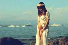 Bella donna incinta che porta un vestito bianco Immagini Stock