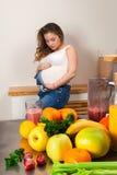 Bella donna incinta che segna il suo stomaco con i frutti nella priorità alta Fotografia Stock