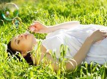 Bella donna incinta che si rilassa sull'erba Fotografia Stock