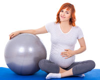 Bella donna incinta che si siede con il fitball isolato sul bianco Fotografia Stock