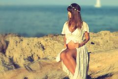 Bella donna incinta che si siede sulla spiaggia Immagine Stock Libera da Diritti