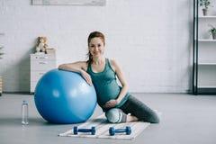 bella donna incinta che si siede sulla stuoia di yoga e che si appoggia la palla di forma fisica fotografia stock libera da diritti