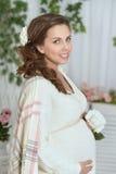 Bella donna incinta con la rosa di bianco Immagini Stock