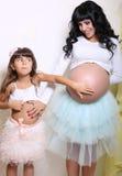 Bella donna incinta con la sua piccola figlia divertente Fotografie Stock