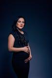 Bella donna incinta con trucco luminoso, capelli neri lunghi, in un vestito dal nero-montaggio che posa in uno studio della foto Immagini Stock Libere da Diritti
