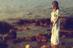 Bella donna incinta sulla spiaggia Immagine Stock