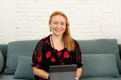 Bella donna indipendente sicura felice che lavora a casa con la compressa sulla sua nuova società online fotografie stock