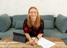 Bella donna indipendente sicura felice che lavora a casa con la compressa sulla sua nuova società online fotografia stock