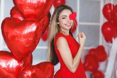 Bella donna intelligente con i palloni rossi il giorno del ` s del biglietto di S. Valentino Fotografia Stock