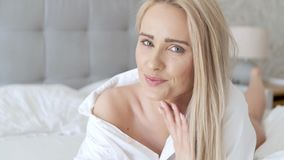 Bella donna invecchiata media che si trova sul letto, sulla camicia bianca d'uso e sul sorridere video d archivio