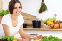 Bella donna ispana che cucina mentre utilizzando il computer della compressa nella cucina Nuova ricetta trovata casalinga per la  fotografia stock
