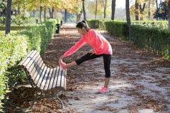 Bella donna ispanica di sport in abiti sportivi che allungano gamba sulla b Immagini Stock
