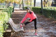 Bella donna ispanica di sport in abiti sportivi che allungano gamba sulla b Immagine Stock