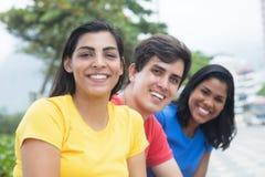 Bella donna latina in una camicia gialla con gli amici Immagini Stock