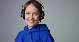 Bella donna in maglia con cappuccio blu che mette sulle cuffie stock footage