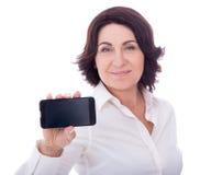 Bella donna matura che mostra telefono con lo schermo in bianco isolato Immagini Stock