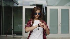 Bella donna moderna in occhiali da sole che aspettano e che controllano tempo sul suo orologio vicino al centro dell'ufficio archivi video