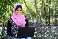 Bella donna musulmana che per mezzo del computer portatile Fotografia Stock Libera da Diritti