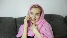 Bella donna musulmana nel hijab rosa che si siede su un sofà in un caffè e che parla sul telefono cellulare video d archivio