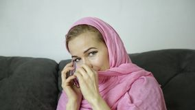 Bella donna musulmana nel hijab rosa che si siede su un sofà in un caffè e che parla sul telefono cellulare stock footage