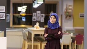 Bella donna musulmana in un vestito orientale moderno che sta nell'atrio del ristorante video d archivio