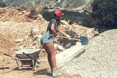 Bella donna negli shorts e in rosso cappuccio alzato con una carriola per cemento e la pala che scavano sulla pietra Concetto Fotografia Stock