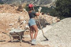 Bella donna negli shorts e in rosso guanti di lavoro d'uso alzati del cappuccio per lavorare duro al cantiere