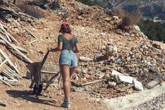 Bella donna negli shorts e in rosso nel cappuccio alzato che tengono una carriola per cemento
