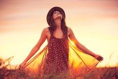 Bella donna nel campo dorato al tramonto immagini stock