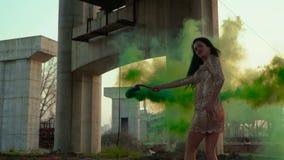 Bella donna nel dancing del vestito con il fumo verde video d archivio