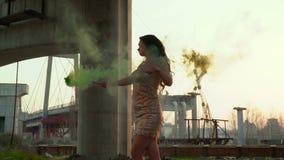 Bella donna nel dancing dorato del vestito con il chiarore verde del fumo archivi video