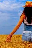 Bella donna nel giacimento della segale sul cielo blu immagine stock