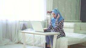 Bella donna nel hijab al computer a casa con una cuffia avricolare, lavoro a distanza su Internet, call center stock footage