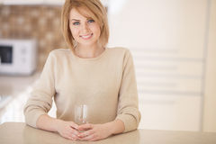 Bella donna nella cucina con un bicchiere d'acqua Fotografia Stock Libera da Diritti