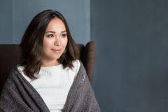 Bella donna nella stanza avvolta in una seduta generale del plaid in poltrona che sogna e che progetta la sua vacanza di autunno Fotografia Stock