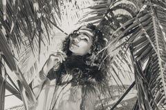 Bella donna nella tonalità della palma sulla spiaggia Immagine Stock