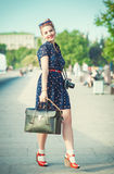 Bella donna nello stile di anni '50 con i ganci che tengono retro camer Fotografia Stock Libera da Diritti