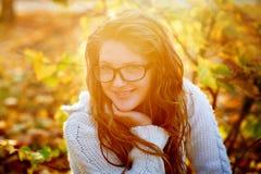 Bella donna in occhiali da sole che cammina nel parco di autunno su un fondo di fogliame giallo fotografia stock libera da diritti