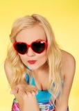 Bella donna in occhiali da sole che inviano un bacio Fotografia Stock