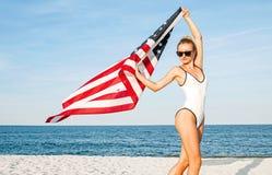 Bella donna patriottica che tiene una bandiera americana sulla spiaggia Festa dell'indipendenza di U.S.A., il 4 luglio immagini stock