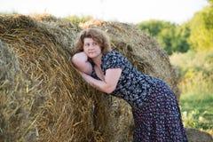 Bella donna pensierosa nel campo con le balle della paglia Fotografia Stock