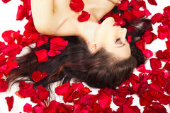 Bella donna in petali delle rose rosse sopra bianco Fotografia Stock